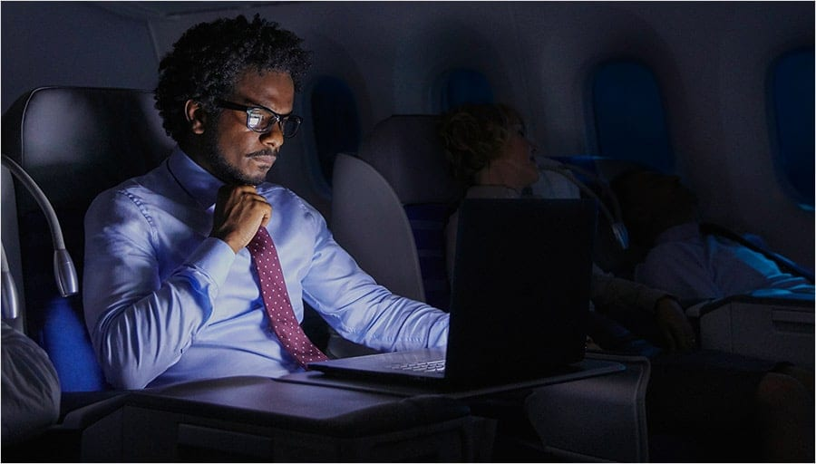 Photo of a man using a laptop on an airplane.
